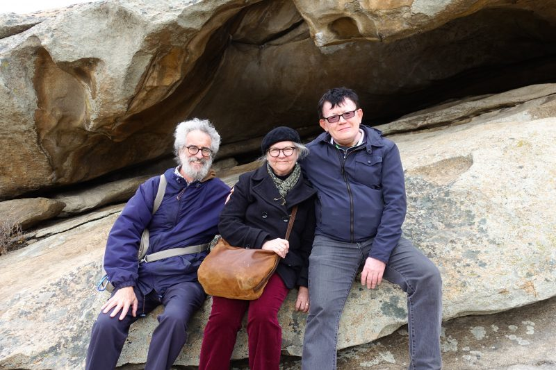 Rich Burke, his wife Beth Packert, and Serik Abilov sitting on a rock.