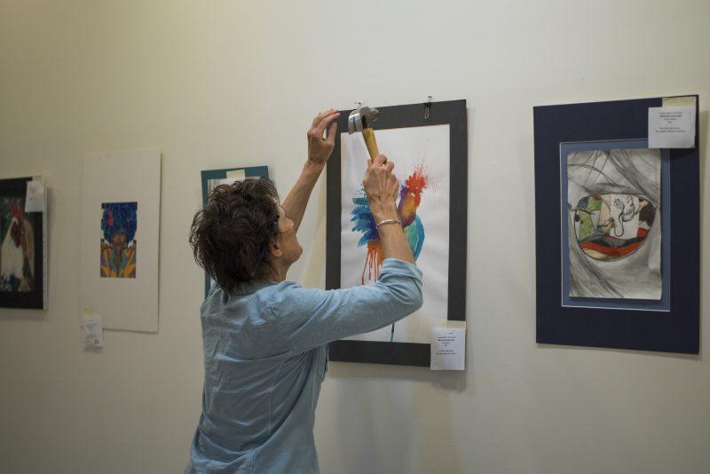 Professor hanging art on the wall