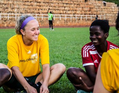 Photo of soccer players sitting on a field and talking after a game.