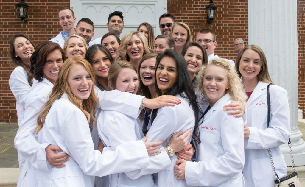 A group of more than 20 students wearing white coats are gathered on the front porch of Snidow Chapel.