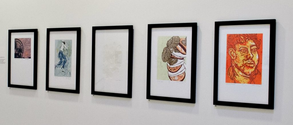 Picture of five artistic prints hanging on a wall.