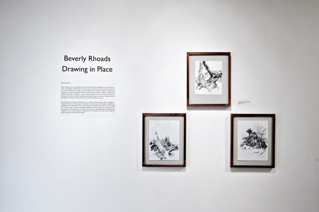 "Photo of three drawings hanging on a wall, as well as a sticker containing the words, ""Beverly Rhoads, Drawing in Place,"" and the artists statement about the exhibition."