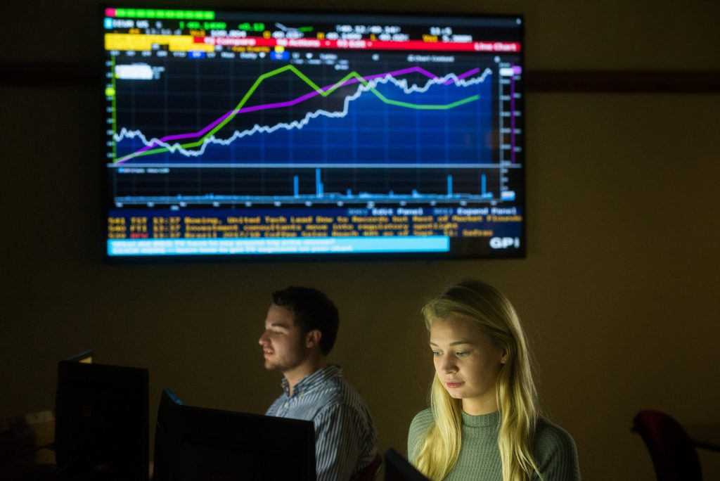 Photo of two students sitting at computers as a large monitor behind them displays graphs illustrating financial information.