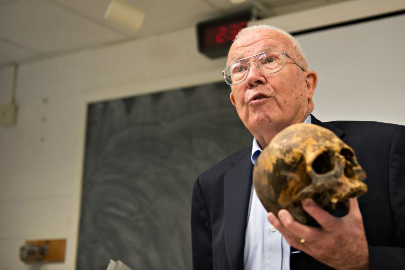 Photo of Dr. William Bass holding a skull. A chalkboard is in the background.