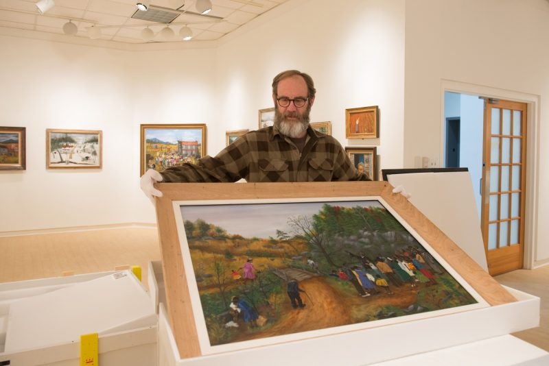 Steve Riffee, assistant director of the Daura Gallery, carefully removes a Stovall painting from its shipping crate.