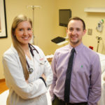Two DMSc graduates, one in a white doctor coat and the other in business attire, in a clinic room