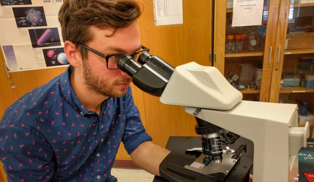 Colby Phillips looks through a microscope