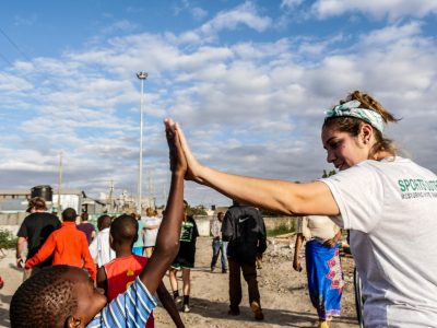 A University of Lynchburg womens soccer athlete gives a high five to a young boy in Africa.