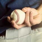 Baseball pitcher holding a ball.