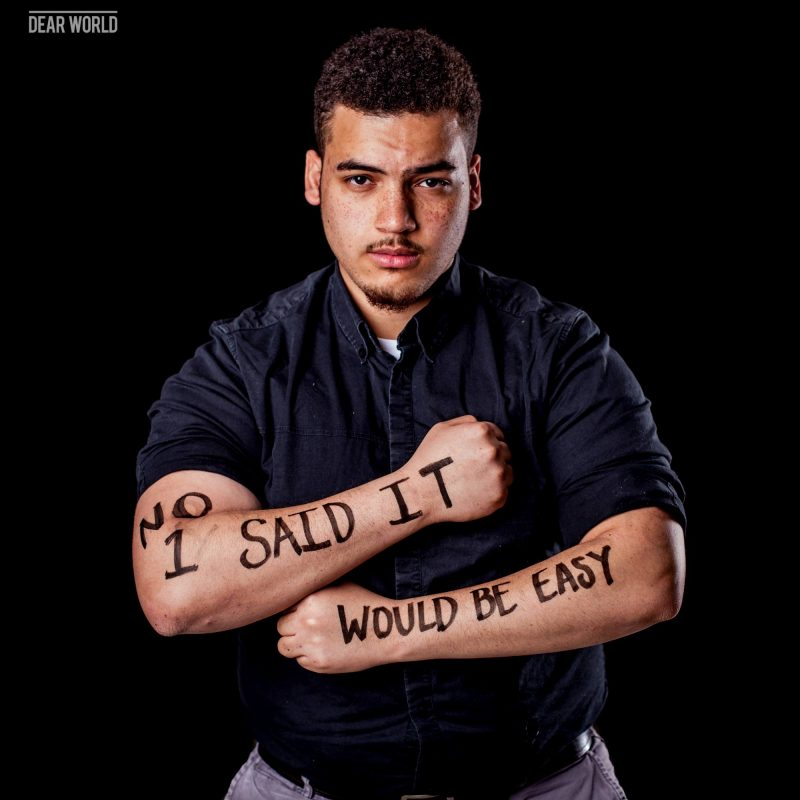 "A man with the message ""No 1 said it would be easy"" written on his arms."