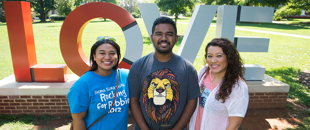Three students in front of the LC Love sculpture