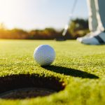 Golf ball sits near the hole on the green as golfer shoes and a golf club are seen in the background.