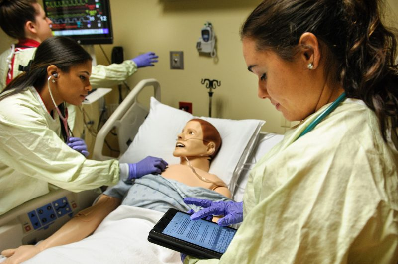 "Nursing students using an iPad tablet in a simulation center. One of the students is ""treating"" a mannequin."
